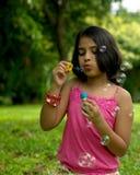 Bolhas de sopro da menina no jardim imagem de stock royalty free