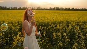 Bolhas de sopro da mulher nova do vermelho-cabelo na câmera fora no prado do verão video estoque