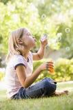 Bolhas de sopro da rapariga ao ar livre Fotografia de Stock Royalty Free