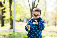 Bolhas de sopro do menino no parque foto de stock royalty free