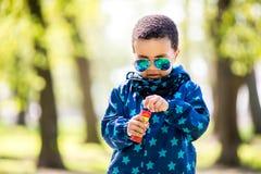 Bolhas de sopro do menino no parque foto de stock