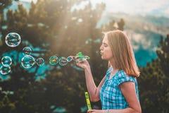 Bolhas de sopro fêmeas bonitas no por do sol fotografia de stock