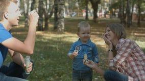 Bolhas de sopro felizes da mãe, do pai e do filho no parque imagens de stock