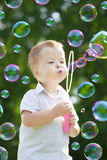 Bolhas do sopro da criança fotografia de stock royalty free