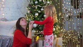Bolhas do sopro da mãe e da filha perto da árvore de Natal filme