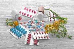 Bolhas, garrafas com comprimidos coloridos e ervas Imagens de Stock