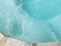 Bolhas na água de turquesa de uma banheira de hidromassagem com opinião superior da borda da rocha Fotografia de Stock