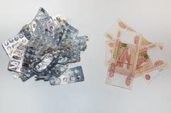 Bolhas vazias dos comprimidos e muitas contas do rublo em um fundo branco O conceito do custo alto das drogas fotos de stock royalty free