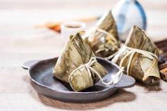 Bolinha de massa de Zongzirice com um copo do chá em uma tabela de madeira, Dragon Boat Festival, alimento tradicional asiático imagens de stock royalty free