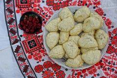 Bolinhas de massa caseiros e preservação das cerejas em uma toalha com um teste padrão do folclore foto de stock