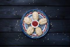 Bolinhas de massa cozinhadas tradicionais Manti na placa com o ornamento oriental com molho de tomate Vista superior Fundo de mad Fotos de Stock