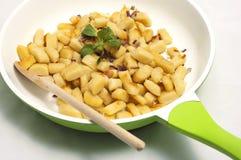 Bolinhas de massa da batata na frigideira verde com colher de madeira Fotos de Stock Royalty Free