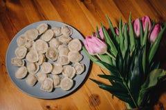 Bolinhas de massa e um ramalhete de tulipas cor-de-rosa em um fundo de madeira imagens de stock royalty free
