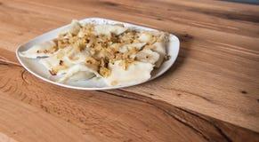 Bolinhas de massa em uma placa com cebolas fritadas Imagens de Stock Royalty Free