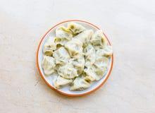 Bolinhas de massa em uma placa redonda, especialidades chinesas, alimento nas placas de mármore brancas fotografia de stock royalty free