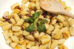Bolinhas de massa pequenas da batata do close-up com cebola fritada e o spoo de madeira Fotos de Stock Royalty Free