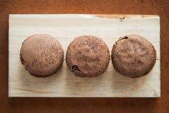 Bolinho de amêndoa do sabor do chocolate colocado na madeira e no couro Fotos de Stock Royalty Free