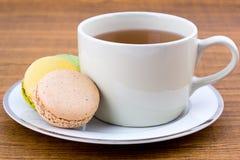 Bolinho de amêndoa e xícara de chá na tabela de madeira Fotografia de Stock