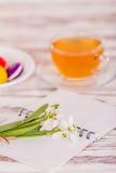 Bolinho de amêndoa, um copo do chá e flores na tabela imagem de stock