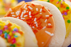 Bolinhos de açúcar geados amarelos e alaranjados com Sprin Fotografia de Stock Royalty Free