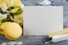 Bolinhos de amêndoa amarelos com as flores no fundo Fotos de Stock