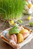 Bolinhos de amêndoa coloridos das merengues em ovos da páscoa de uma cesta de vime fotos de stock royalty free