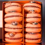 Bolinhos de amêndoa coloridos e saborosos na caixa de papel com alianças de casamento Imagem de Stock