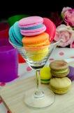 Bolinhos de amêndoa coloridos em um vidro no fundo de madeira Fotografia de Stock Royalty Free