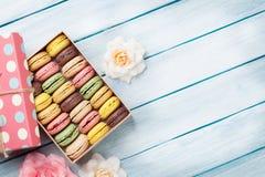 Bolinhos de amêndoa coloridos em uma caixa de presente e em rosas Fotos de Stock