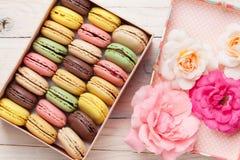 Bolinhos de amêndoa coloridos em uma caixa de presente e em rosas Fotos de Stock Royalty Free