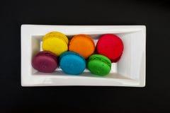 Bolinhos de amêndoa coloridos em uma placa branca Imagens de Stock