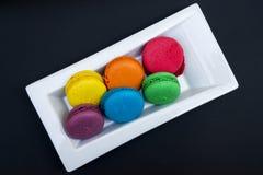 Bolinhos de amêndoa coloridos em uma placa branca Fotografia de Stock Royalty Free
