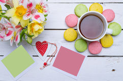 Bolinhos de amêndoa coloridos, flores, cartões, e um copo do chá quente sobre Fotografia de Stock Royalty Free