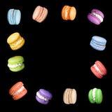 Bolinhos de amêndoa coloridos isolados no fundo preto que cai ou que voa no movimento Macarons franceses tradicionais da sobremes Fotografia de Stock Royalty Free