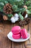Bolinhos de amêndoa cor-de-rosa com as decorações do Natal no fundo de madeira Imagem de Stock