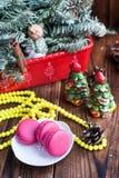 Bolinhos de amêndoa cor-de-rosa com as decorações do Natal no fundo de madeira Fotos de Stock
