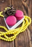 Bolinhos de amêndoa cor-de-rosa com as decorações do Natal no fundo de madeira Imagens de Stock