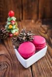 Bolinhos de amêndoa cor-de-rosa com as decorações do Natal no fundo de madeira Fotografia de Stock Royalty Free