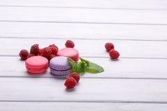 Bolinhos de amêndoa cor-de-rosa com framboesas e hortelã no fundo branco Foto de Stock
