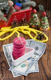 Bolinhos de amêndoa cor-de-rosa e vinte dólares com as decorações do Natal no fundo de madeira Imagem de Stock Royalty Free