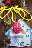 Bolinhos de amêndoa cor-de-rosa e vinte euro com as decorações do Natal no fundo de madeira Imagem de Stock Royalty Free