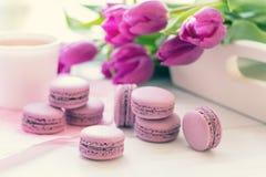 Bolinhos de amêndoa deliciosos doces violetas e tulipas frescas Fotografia de Stock Royalty Free