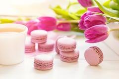 Bolinhos de amêndoa deliciosos doces violetas e tulipas frescas Fotos de Stock Royalty Free