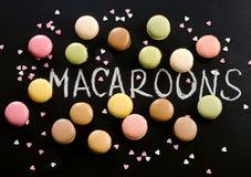 Bolinhos de amêndoa doces coloridos no fundo preto Foto de Stock