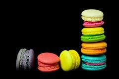Bolinhos de amêndoa doces e coloridos no fundo preto Foto de Stock