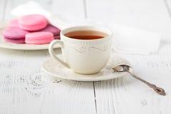 Bolinhos de amêndoa e copo franceses coloridos do chá em uma parte traseira de madeira rústica Fotos de Stock