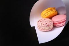 Bolinhos de amêndoa franceses doces e coloridos no fundo preto Imagens de Stock Royalty Free