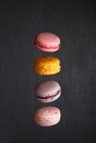 Bolinhos de amêndoa franceses doces e coloridos no fundo preto Fotografia de Stock Royalty Free
