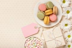 Bolinhos de amêndoa, marshmallows, caixa do git e flores coloridos franceses Imagens de Stock Royalty Free