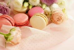 Bolinhos de amêndoa nas cores pastel com flores em um pálido - fundo cor-de-rosa Fundo do feriado foto de stock royalty free